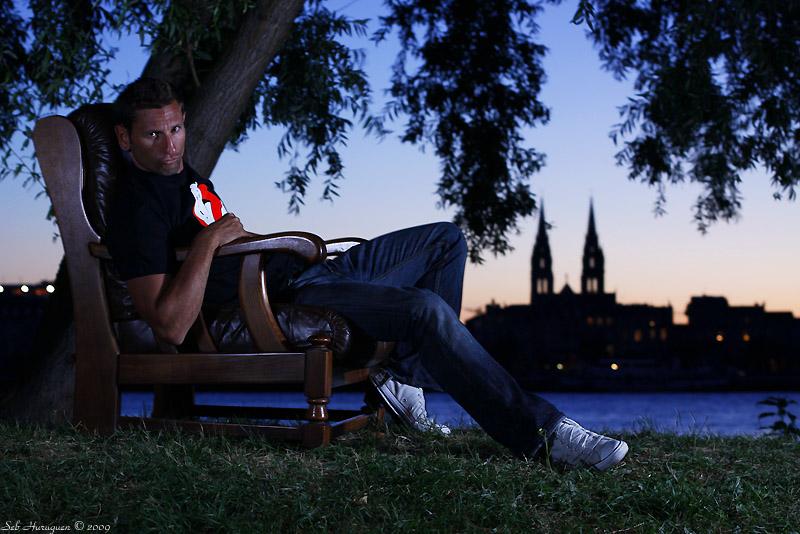 Portrait d'une jeune homme dans un fauteuil en cuir sur les bords de garonne à Bordeaux rive droite